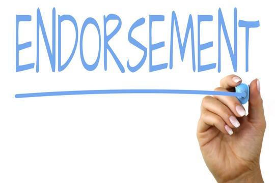Tangan sedang menulis kata Endorsement: Trik Memilih Endorser yang Tepat